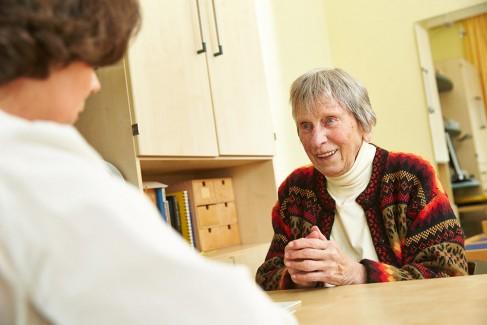Eine lächelnde Rentnerin in einer Unterhaltung mit einer Therapeutin