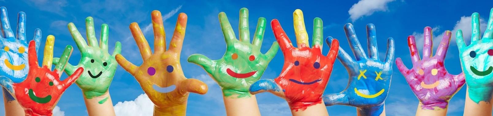 Bunte Kinderhände mit aufgemalten Smileys vor einem Himmel